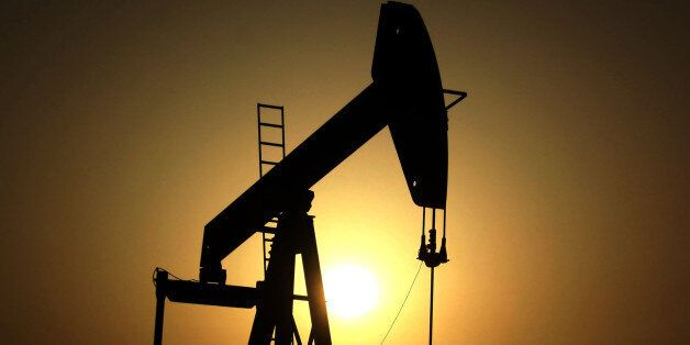 FILE- In this Wednesday, June 8, 2011 file photo, sun sets behind an oil pump in the desert oil fields...