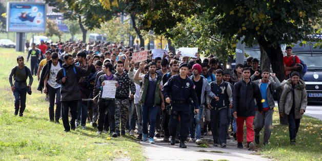 Several hundred refugees and migrants walk heading in the direction of the Hungarian border, in Belgrade,...