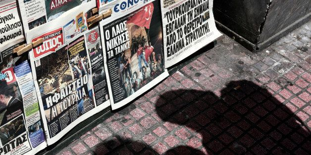 Two men cast their shadows as they check newspapers outside a kiosk in Athens, on Saturday, July 16,...