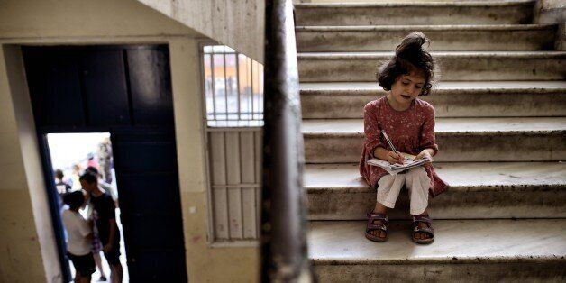 A young girl drawsas she sits in the stairs of an abandoned school used by volunteers for hosting Syrian...