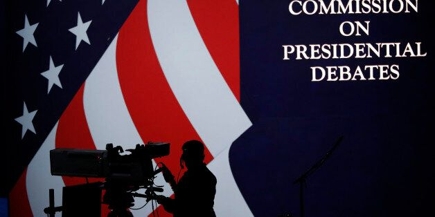 A cameraman is silhouetted against an an American flag during preparations for the presidential debate...