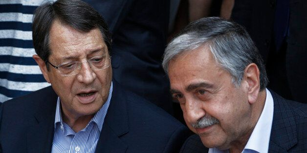 Cyprus President Nicos Anastasiades, left, and Turkish Cypriot leader Mustafa Akinci, speak as they sit...