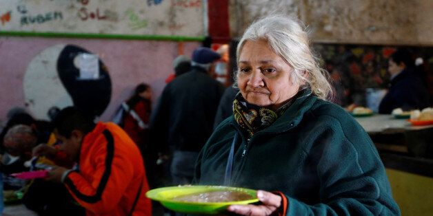 A woman carries a meal at the Bokitas free community soup kitchen in a neighborhood of Buenos Aires,...