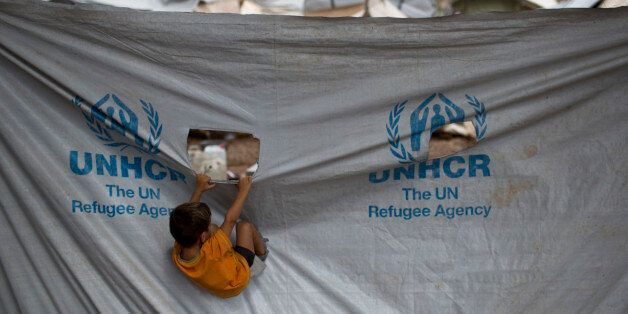 A child play in front of a UNHCR plastic sheet at Ritsona refugee camp, north of Athens, which hosts...