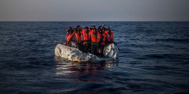 In this photo taken on Saturday Sept. 10, 2016, African refugees and migrants wait aboard a partially...