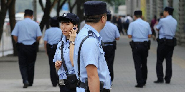 Policemen secure the area near the Beijing Number 2 People's Intermediate Court where the sentencing...