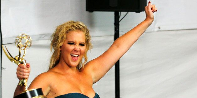 Comedian Amy Schumer enters the photoroom with her award for Outstanding Variety Sketch Series for Comedy
