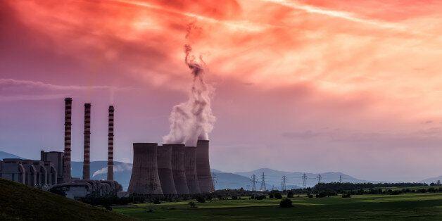 Electric power plant at dusk with orange sky in Kozani