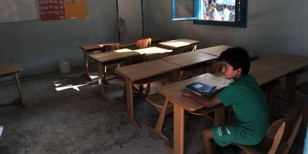 A child sits in a classroom in the refugee camp of Lagadikia, some 40km North of Thessaloniki, during...