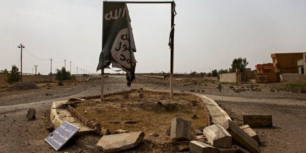 In this Sunday, August 28, 2016 photo, a partially destroyed Islamic State group banner hangs at the...