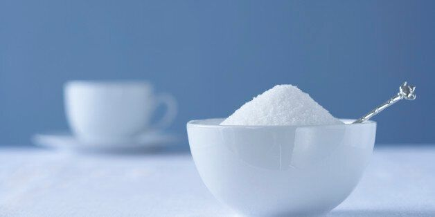 Bowl of sugar on table, tea cup in
