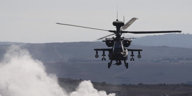 An AH-64 Apache helicopter flies over smoke while taking part in Exercise Trident Juncture 2015, NATO's...