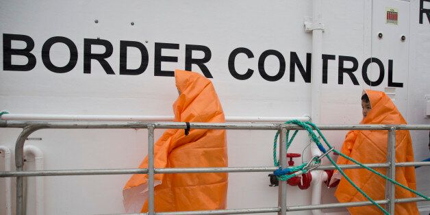 Two children prepare to disembark with other 53 migrants and refugees from a Norwegian Frontex patrol...