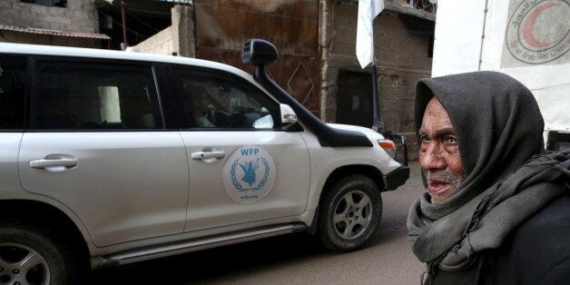 An elderly man stands along a street as he looks at an aid convoy of Syrian Arab Red Crescent and United...