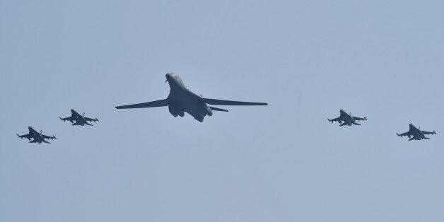 A US B-1B Lancer (C) is escorted by US F-16 fighter jets as it flies over the Osan Air Base, aiming at...