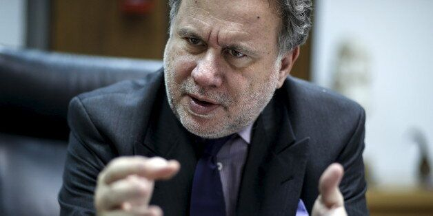 Greek Labour Minister George Katrougalos gestures during an interview with Reuters at his office at the...