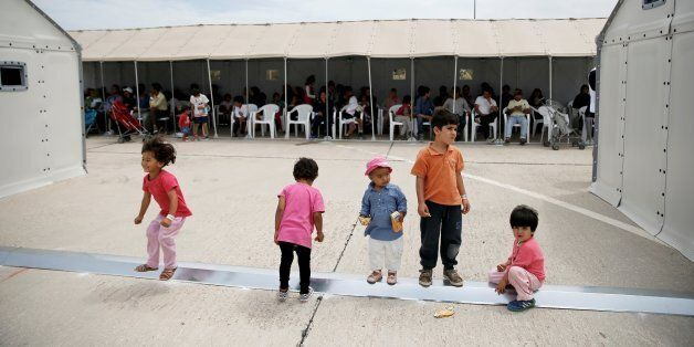 Children play as refugees and migrants wait to take part in a pre-registration process that gives them...