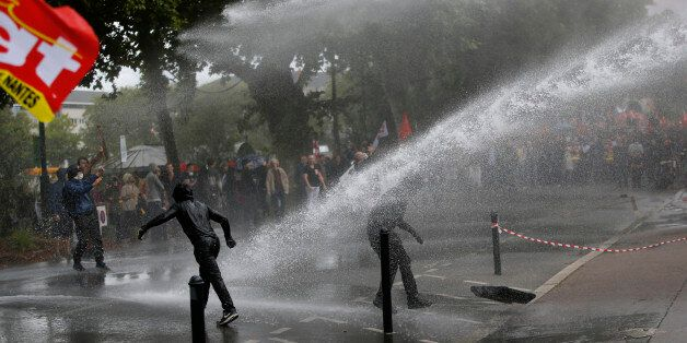Demonstrators are sprayed by a water canon during clashes with French riot police at a march in Nantes,...