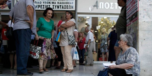 Pensioners wait outside Greece's largest Social Security Organisation (IKA) in Athens, Friday, May 31,...