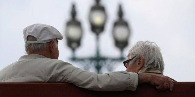 A retired couple sits on a bench in Enghien-les-Bains, north of Paris, August 26, 2013. France's government,...