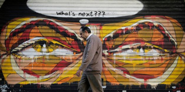 In this photo made on Tuesday, April 29, 2015, a Greek man walks past a graffiti in central Athens. Wednesday...