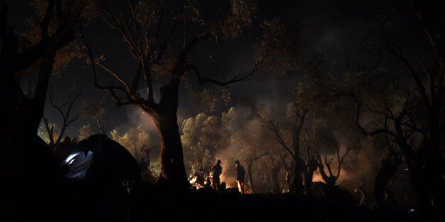 Refugees and migrants spend the night in a field outside of the Moria Hot Spot, on the Greek island of...