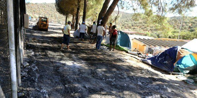 Workers clean the area after a fire gutted the camp following protests at the Moria refugee camp on the...