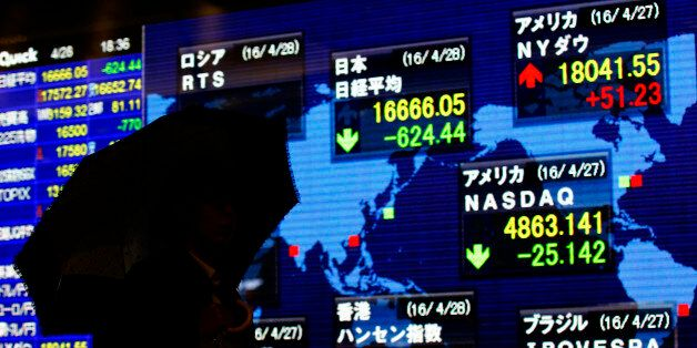 FILE - In this April 28, 2016 file photo, a man looks at an electronic stock indicator of a securities...
