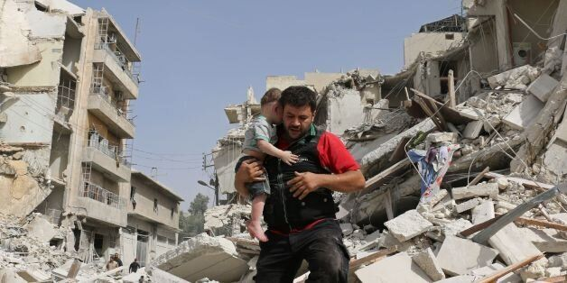 A Syrian man carries a baby after removing him from the rubble of a destroyed building following a reported...