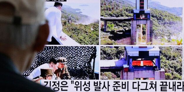A man watches a TV news showing images that North Korea's Rodong Sinmun newspaper reports of the ground...