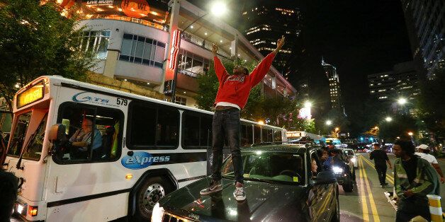 A man stands on a car in uptown Charlotte, NC to protest the police shooting of Keith Scott, in Charlotte,...