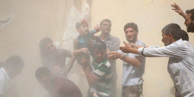 ALEPPO, SYRIA - JULY 17: (EDITOR'S NOTE: Image contains graphic content.) A Syrian man carries a wounded...