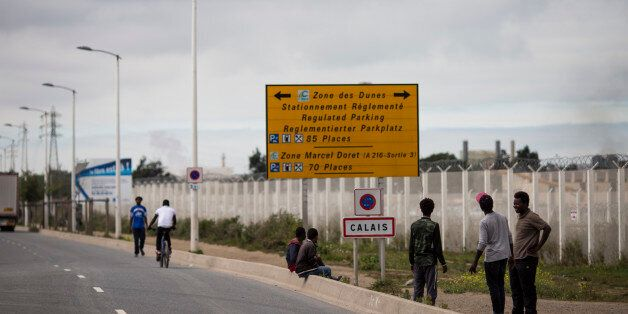CALAIS, FRANCE - SEPTEMBER 06: Migrants by a Calais road sign outside the Jungle migrant camp on September...