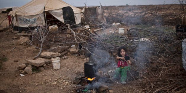 FILE -- In this Oct. 23, 2015 file photo, Syrian refugee Aysha Elwan, 5, helps her mother in breaking...
