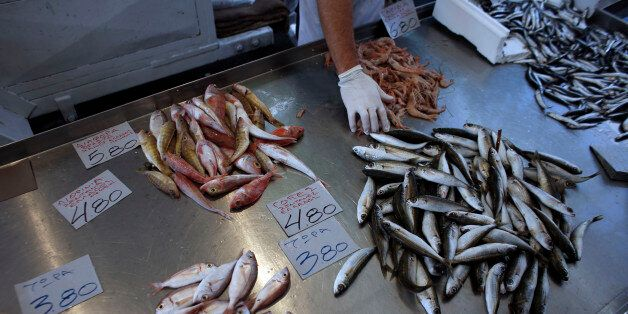 Fresh fish sit for sale beside euro price signs at a street market in Athens, Greece, on Thursday, Nov....