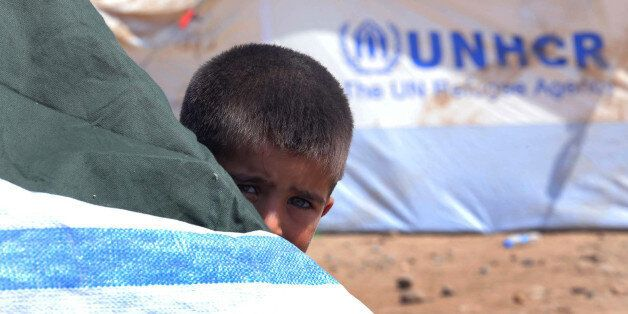 A Syrian refugee boy peeps behind a tent at the Quru Gusik refugee camp on the outskirts of Arbil in...