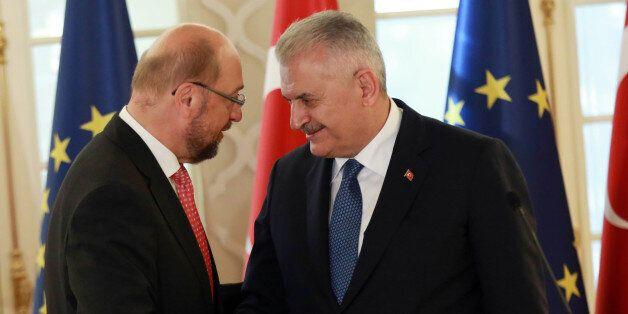 President of the European Parliament Martin Schulz (L) shakes hands wiyj Turkish Prime Minister Binali...