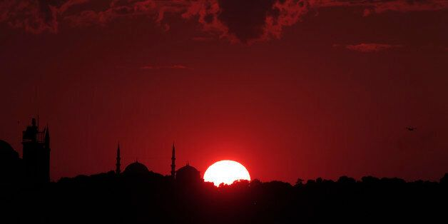 The sun sets behind Istanbul's skyline, Tuesday, July 14, 2015. Istanbul is a thoroughly modern place,...