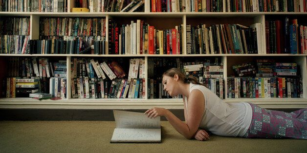 Young woman lying on floor by book shelves, reading, side