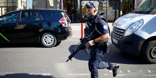 A police officer runs to take position during a bomb scare at Gare de Lyon railway station in Paris,...