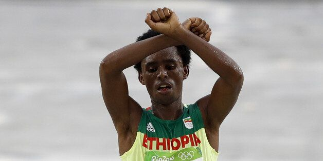 TOPSHOT - Ethiopia's Feyisa Lilesa (silver) crosses the finish line of the Men's Marathon athletics event...