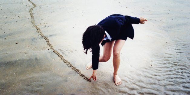 Young businesswoman drawing line in sand on beach