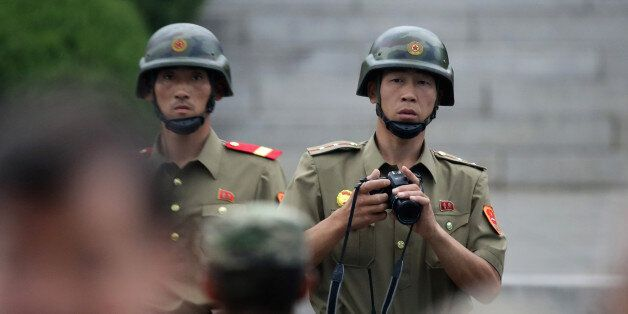 PANMUNJOM, SOUTH KOREA - JULY 27: North Korean soldiers look on as South Korean and United Nation officials...