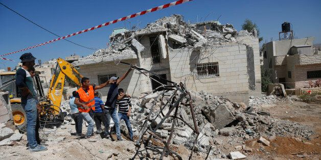 Palestinians clean the debris at the family house of Khaled Mahamra after it was demolished by Israeli...