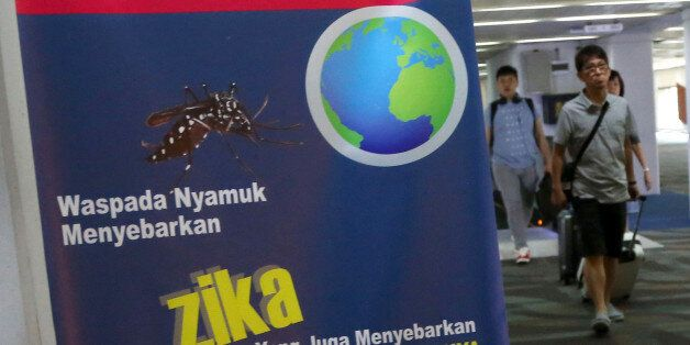 Arriving travelers walk past an nformation banner on Zika virus at Soekarno-Hatta International Airport...