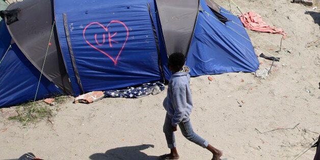 A heart and UK symbol are marked on the side of a tent as a migrant walks in the make-shift camp, called...