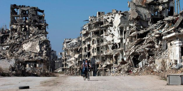 A Syrian boy rides a bicycle through a devastated part of the old city of Homs, Syria, Friday, Feb. 26,...
