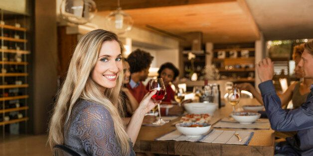 Smiling woman holding a glass at a table having dinner with