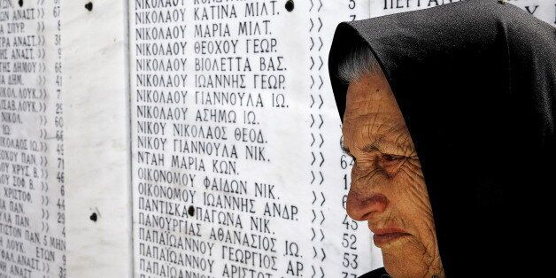 Survivor Loukia Gavrili, 86, sits by a plaque featuring the names of those killed by Nazi troops, on...