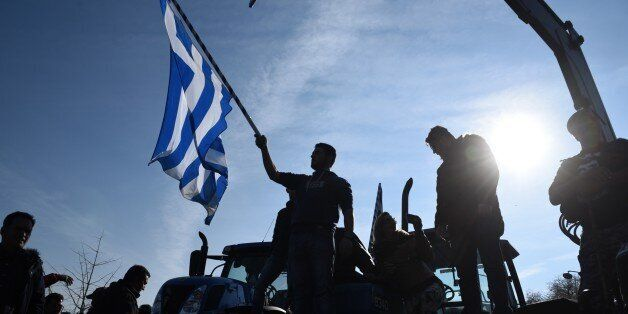 In this Thursday, Jan. 28, 2016, file photo a protesting farmer waves a Greek flag during a rally in...